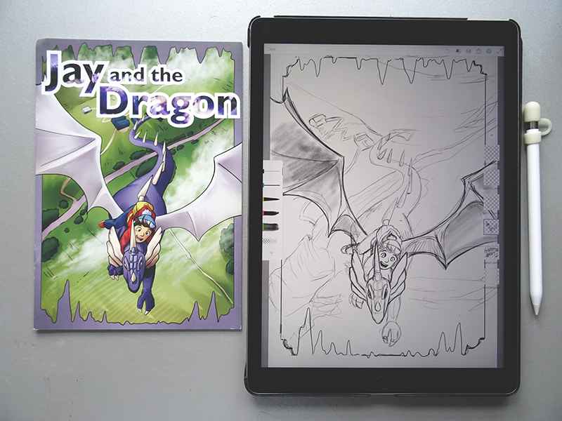 The printed comic next to pencil work on an iPad.